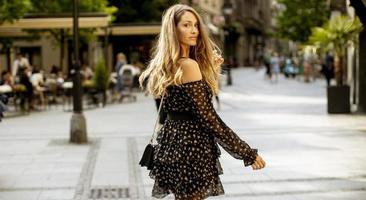 ung brunettkvinna för långt hår som går på gatan foto