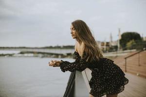 ung brunettkvinna för långt hår som står på flodstranden foto