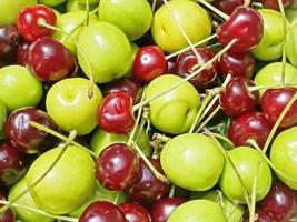 redo att äta och tvättade surkörsbär och plommon på en grön tallrik foto