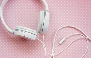 vita hörlurar på rosa bakgrund foto