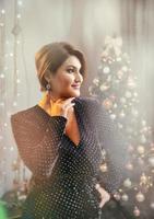 julskytte. vacker modell med nyårsgåvor på bakgrund av ett julgran. foto