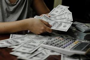 affärsmän kvinnor räknar pengar på en bunt med 100 dollar sedlar mycket pengar foto