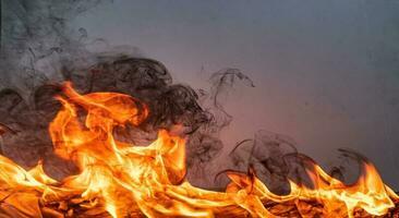 eldslågor med rök på svart bakgrund foto