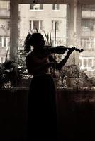 silhuett av en ung flicka, en musiker. spelar fiol i fönstrets bakgrund foto