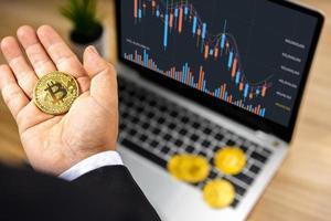 affärs bitcoin till hands för investerare med grafdiagram på bärbar dator på träbord, aktiemarknad och valutafinansieringskoncept foto