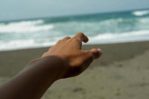 foto av människor som sträcker sin vänstra hand mot havet