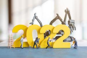 miniatyr människor arbetare team bygga nummer 2022 foto