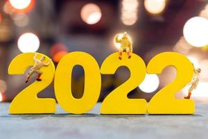 miniatyrfolk som klättrar upp på trä med nummer 2022 foto