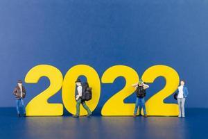 miniatyr människor backpacker stående på trä nummer 2022 foto