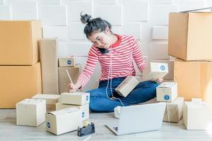 asiatisk kvinnaföretagare som arbetar hemma med förpackningslådan på arbetsplatsen - online-shopping sme-entreprenör eller frilansarbetsbegrepp foto