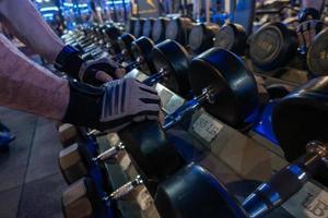 män som håller hanteln i hyllorna i gymmet för träning foto