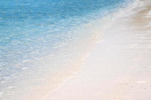 klara havsvågor och vit sandstrand på sommaren. foto