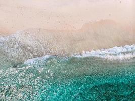 Flygfoto över klara havsvågor och vita sandstränder på sommaren. foto