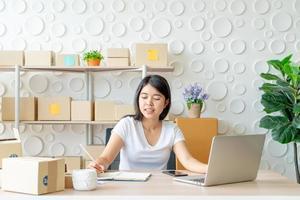 ung asiatisk kvinna som startar upp småföretagare som arbetar med den digitala minnestavlan på arbetsplatsen - online-försäljning, e-handel, fraktbegrepp foto