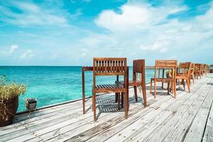 Tom utomhus trä bord och stol med havsutsikt bakgrund i Maldiverna foto