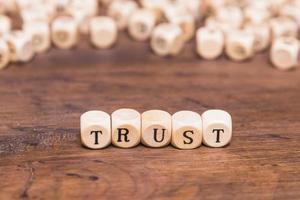förtroendeord med träklossar. högkvalitativt vackert fotokoncept foto