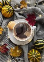 kopp kaffe, torra löv och halsduk på ett bord foto