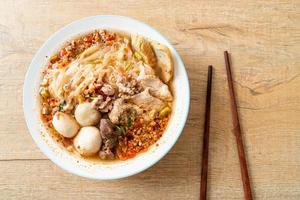 nudlar med fläsk och köttbullar i kryddig soppa eller tom yum nudlar i asiatisk stil foto