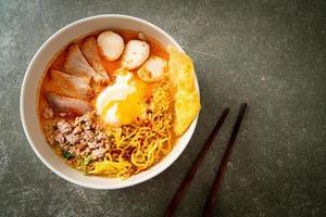 äggnudlar med fläsk och köttbulle i kryddig soppa eller tom yum nudlar i asiatisk stil foto