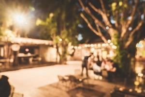 abstrakt suddig utomhus hangout innergård i café restaurang på natten för bakgrund foto