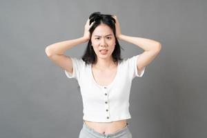 ung asiatisk kvinna med allvarligt och ansträngande ansikte i vit skjorta på grå bakgrund foto