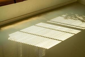 vackert solljus och solblind skugga på golvet foto