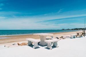 utomhusbord och stol med havsstrand och bakgrund för blå himmel foto