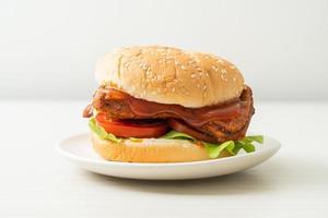 grillad kycklingburger med sås på den vita plattan foto