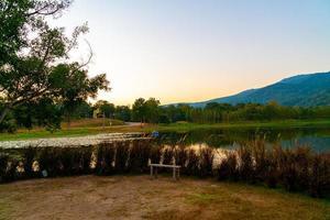 träbänk med vacker sjö vid Chiang Mai med skogsklädda berg och skymningshimmel i Thailand. foto