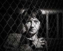 porträtt av en ung flicka bakom staketet foto