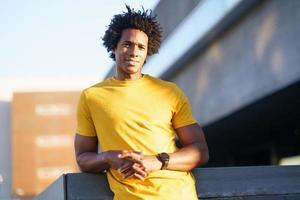 svart man med afrohår som tar en paus efter träning. foto
