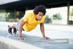 svart man gör triceps dopp övning på staden gatan bänk. foto