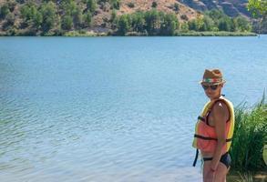 kvinna i hatt och flytväst som står vid floden foto
