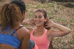 fitnesskvinnor som övar yoga i en park. kvinnor som gör träningspass i en park. foto