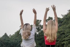 två kvinnor som står och reser sig upp i parken. bästa vänner foto