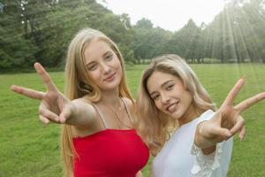 två kvinnliga vänner som har kul i parken. foto