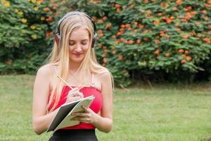 vacker ung kvinna skriver med anteckning på park foto