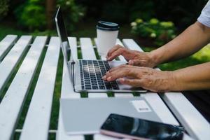 händer på nära håll av den gamla mannen som använder bärbara datorn foto