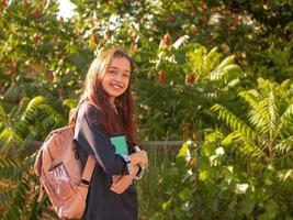 skolflicka tonåring flicka leende med anteckningsblock foto