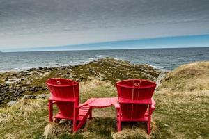 röda stolar vid grön punkt. Gros Morne National Park, Newfoundland, Kanada foto
