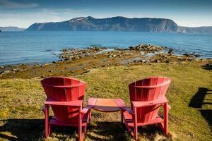 röda stolar och utsikt från gul punkt. Gros Morne National Park, Newfoundland, Kanada foto