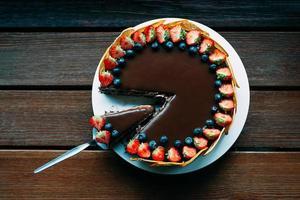 läcker chokladkaka med bär och glasyr, ovanifrån foto