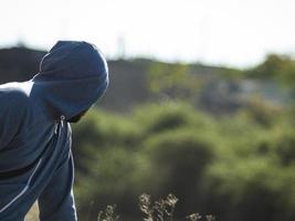 en man med skägg i huven tittar in i fjärran och vänder tillbaka foto