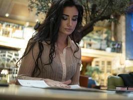 vacker flicka med smink sitter vid bordet och tittar på menyn foto