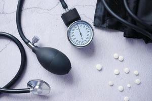 ovanifrån av blodtrycksmaskin och medicinskt piller på bordet. foto