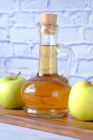 äppelvinäger i glasflaska med färskt grönt äpple på bordet foto