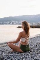 ung kvinna som mediterar på stranden foto