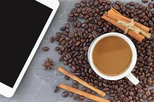 kaffebönor och minnestavladator på stenbakgrund foto