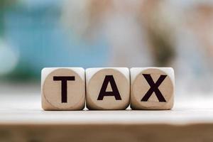 skattekoncept med träkloss på träbordbakgrund foto
