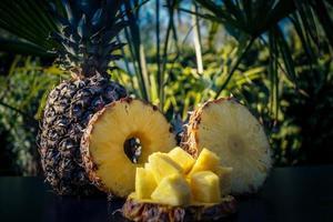skivad ananas framför palmer foto